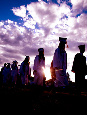 JIM VAIKNORAS/staff photo  The setting suns breaks through the clouds as Amesbury high seniors make their way into graduation at Landry Stadium in Amesbury Friday night.