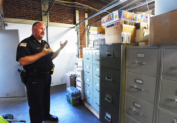 BRYAN EATON/Staff photo. Merrimac police chief Eric Spears in the two-bay garage that's used for storage.