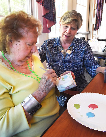 BRYAN EATON/Staff photo. Kathy Ryan, right, of the Pottery Isle came to Brigham Manor Nursing and Rehab Center to work with residents to decorate different pieces of pottery. Here she watches as Betty Reader, who attended art school, decorate a coffee mug.