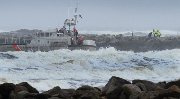 BRYAN EATON/Staff photo. Rescuers take a man up onto the north jetty of Salisbury Beach as the Coast Guard Station Merrimack crew look for a second person that is missing in the rough surf.