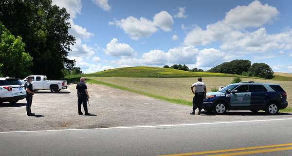 BRYAN EATON/Staff photo. Amesbury and Massachusetts state police gather at Woodsom Farm on Lion's Mouth Road as the search was underway at the Amesbury Town Forest which is beyond the hills in back.