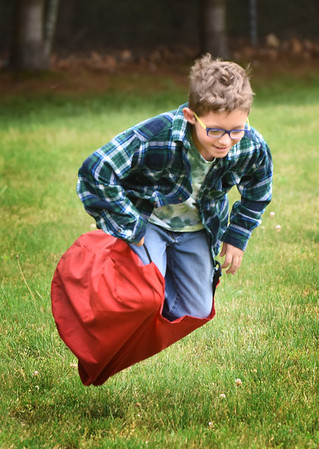 BRYAN EATON/Staff photo. Cam Stone, 8, takes a spill in the sack race but quickly got back up to finish the relay race. He was at Field Day at Salisbury Elementary School.