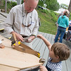 JIMVAIKNORAS/Staff photo Dean Jewett,4, builds a boat with some help from volunteer Bob Adams at teh Lowell Boat Shop Open House in Amesbury Sunday afternoon.