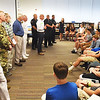 BRYAN EATON/Staff photo. After each of the eleven veterans spoke alone in a classroom of students, they got together in the library with the eighth grade class and introduced themselves and gave a quick description of their service.