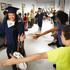 BRYAN EATON/Staff photo. Soon-to-be Triton High graduates get high fives from students as they parade through Salisbury Elementary School where they attended.