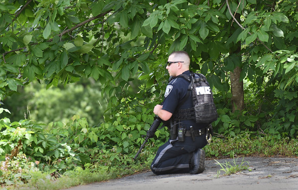 BRYAN EATON/Staff photo. An Amesbury police officer crouches on Kimball Road in Amesbury as a search for an apparent suicidal person with weapons was underway.