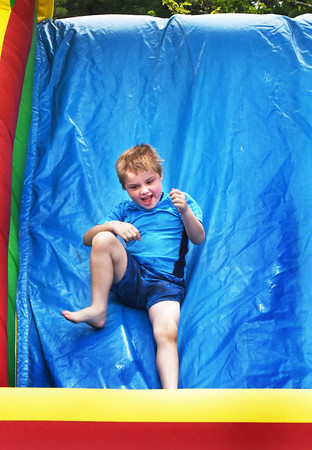 BRYAN EATON/Staff photo. Ian Emmons, 6, of Kensington, N.H. at goes down the slide in the inflatable obstacle course at Amesbury Days Kids Day in the Park. He was there with his mother Karen who grew up in Amesbury.