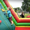 BRYAN EATON/Staff photo. Thomas Smolski, 2, of Amesbury as his mother Aileen takes a photo as he climbs the ladder to the slide of the inflatable obstacle course. They were at Amesbury Days Kids Day in the Park where this amusement was sponsored by the Market Street Baptist Church, All Saint's Church and the Rock Church Ministry.