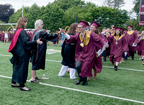 JIM VAIKNORAS/staff photo Valedictorian Jackson Kealey high fives some of his former teacher as he leads his classmates out of graduation at World War Memorial Stadium Sunday morning.