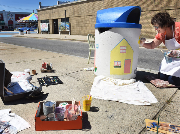 BRYAN EATON/Staff photo. Salisbury resident Diane Masiello decorates one of 65 trash barrels at Salisbury Beach with beach cottages on Wednesday. The improvements are one of many in the beach center as the town readies for Celebrate Salisbury with the opening of the new boardwalk.
