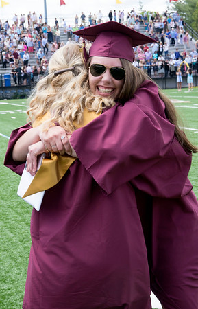 JIM VAIKNORAS/staff photo Katherine Bortz hugs her classmate Rebecca Adams after graduation at World War Memorial Stadium Sunday morning.