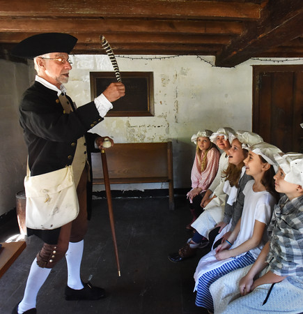 BRYAN EATON/Staff photo. Michael Welch, a museum teacher and historical reenactor shows a quill pen to students from the Bresnahan School in Newburyport in a one schoolroom replica at the Swett-Ilsley House in Newbury. The students are learning about Colonial history and were visiting the various local sites owned by Historical New England.