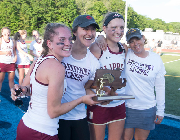 JIM VAIKNORAS/staff photo Newburyport captains Olivia Katavolos, Isabelle Sarra, and Elizabeth Fortier along with coach Catherine Batchelder pose with the Division 2 North Championship trophy at Peabody High School Friday night. Newburyport defeated Ipswich 15-11