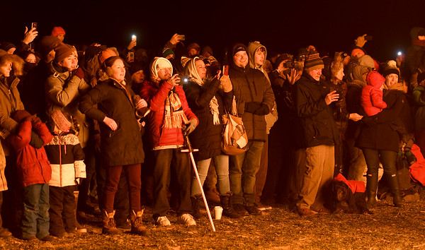 JIM VAIKNORAS/Staff photo The glow from the fire warms the crowd at the Old Newbury Christmas Tree Bonfire at the Tendercrop Farm fields and Spencer Perce-Little Farm in Newbury Saturday night.