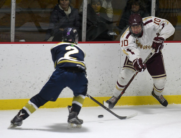 JIM VAIKNORAS/Staff photo Newburyport's Ben Renolds clears the puck past St Mary's Colin Reddy at the Graf Rink in Newburyport Saturday.