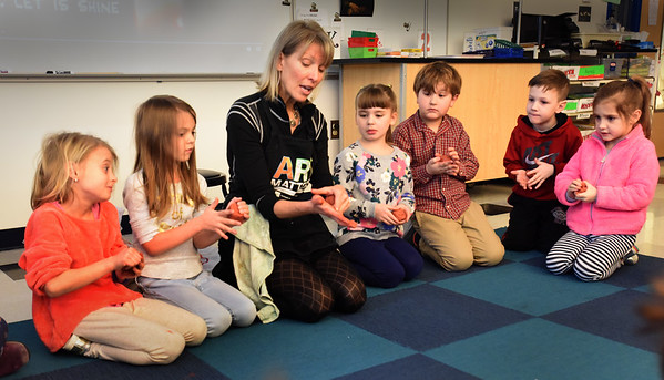 "BRYAN EATON/Staff photo. Bresnahan School artist in residence Kim Salathe has first-graders get a feel for some self hardening clay which doesn't need to be put into a kiln as they prepare to make pinch pots. She brought the ""Mindfullness of Clay"" into art teacher Pamela Jamison's class sponsored the school's PTO."
