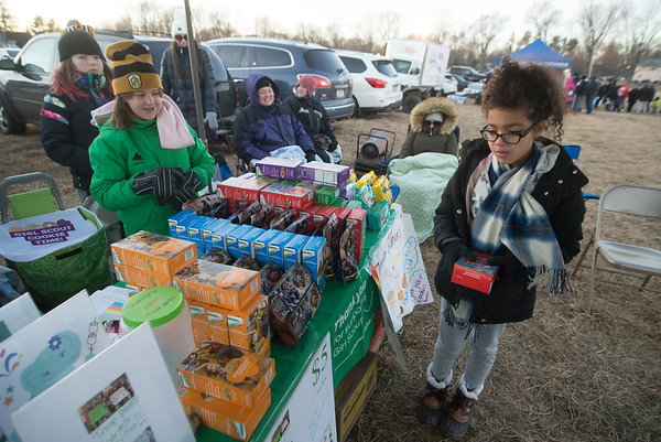JIM VAIKNORAS/Staff photo Maya Mason of Newbury decides on what kind of cookies to buy from Girl Scout Troop 88183 Old Newbury Christmas Tree Bonfire at the Tendercrop Farm fields and Spencer Perce-Little Farm in Newbury Saturday night. She ended up with S'Mores cookies.