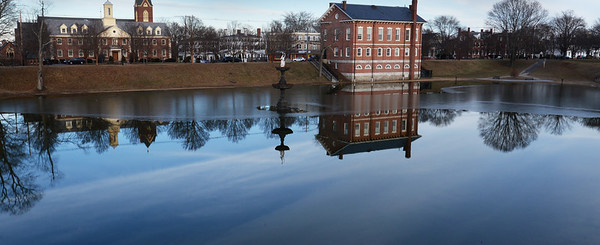 BRYAN EATON/Staff photo. Newburyport Superior Courthouse is reflected off the Frog Pond at the Bartlet Mall as the sky darkens ande showing the ice line. Despite some cold weather, that pond and others haven't frozen over in the new year.