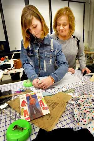 BRYAN EATON/Staff photo. Boys and Girls Club sewing instructor Judy Gaffney looks on as Rory Ciaramecaro, 12, of Amesbury pins the fabric to the pattern of the pajama tank top she's making.