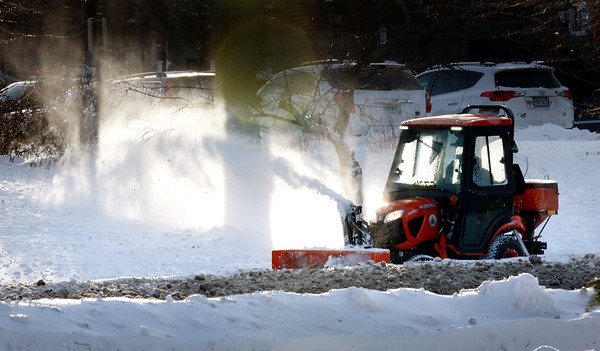 BRYAN EATON/Staff photo. A Newburyport DPS worker uses a snowblower to clean the sidewalk in front of the Green Street parking lot on Tuesday afternoon as the cleanup continued from Sunday's storm. Help is on the way from Mother Nature as temperatures in the 40's and rain is in the forecast to help with melting.