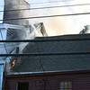 BRYAN EATON/Staff photo. Flame from 155 High Street at left, move to the adjacent row house as firefighter is seen through the smoke.