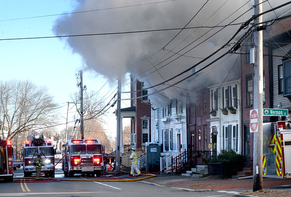 BRYAN EATON/Staff photo. Newburyport firefighters attacked a smoky fire that went to four alarms at 155 High Street, across from St. Paul's Church, which also affected the attached the unit next door.