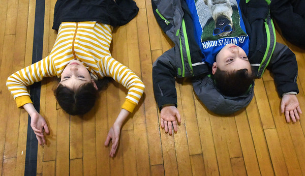 BRYAN EATON/Staff photo. Elle Celano, 8, left, and Ben Cotter, 9, with arms outstretched relax to music and breath slowly on the gym floor during an assembly at Newbury Elementary School. It was part of their wellness initiative to lower and manage stress and will be a part of the start of their school days.