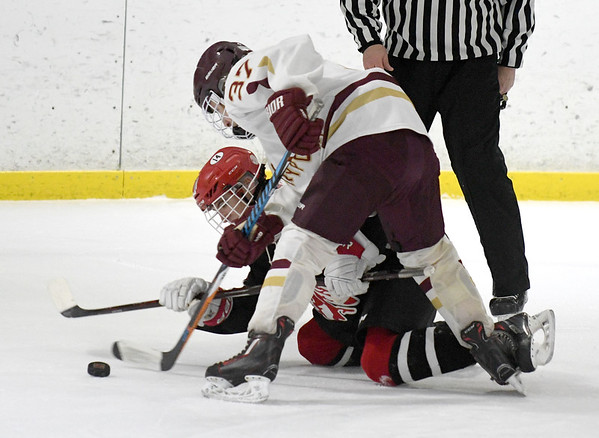 JIM VAIKNORAS/Staff photo Newburyport's Colin Richmond fights for the puck with Amesbury's Nolan McGrath at the Graf Rink in Newburyport Friday.