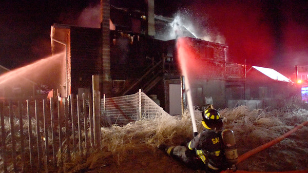 BRYAN EATON/Staff photo. Firefighters extinguish a blaze on 10th Street on the Newbury section of Plum Island witnesses said was #10 late Saturday night.