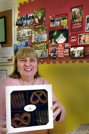 """BRYAN EATON/Staff photo. Pat Perry is closing her Carriagetown Chocolates shop in Amesbury after almost 14 years in business. What she'll miss most is her """"kids"""" in photos above, all the youngsters who would frequent her shop which sold candy as well."""