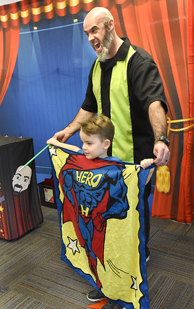 BRYAN EATON/Staff photo. Magician Greg McAdams puts the superhero banner on August Ferris, 4, which he created from four seperate pieces of material with the letters H-E-R and O on each one with the help of Olivia Catalfamo, 8, and a magic wand.