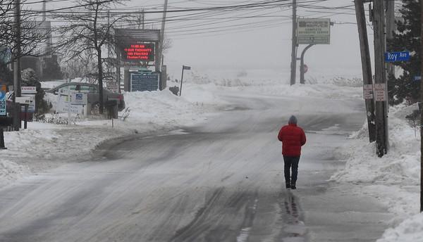 JIM VAIKNORAS/Staff photo A lone figure walks down a newly plowed Plum Island Turnpike in Newbury Sunday afternoon.
