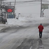 JIM VAIKNORAS/Staff photo A lone figure walks down a newly plowed Plum Island Turnpike in Newbury Sunday afternoon.