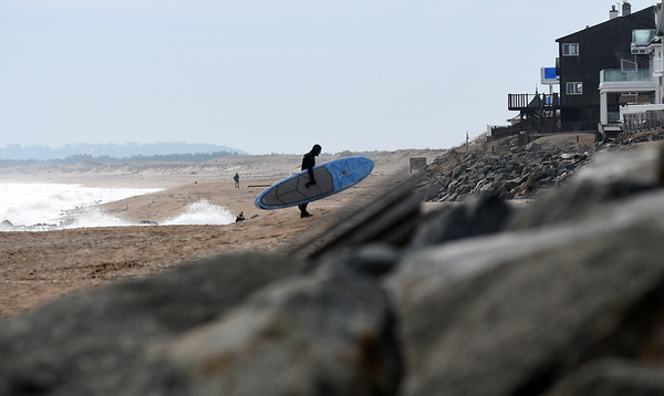 JIM VAIKNORAS/Staff photo A stand up paddle boarder makes his way up the beach on Plum Island Sunday morning.
