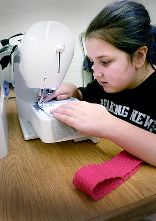 BRYAN EATON/Staff photo. Kamiellia Massote, 10, helped Boys and Girls Club sewing instructor Judy Gaffney organize fabrics and other items for classes next week on Thursday afternoon. When she was finished she worked on making a headband.