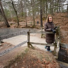 BRYAN EATON/Staff photo. Marlys Edwards atop the dam at Maudslay State Park with the pond it contains to the left.