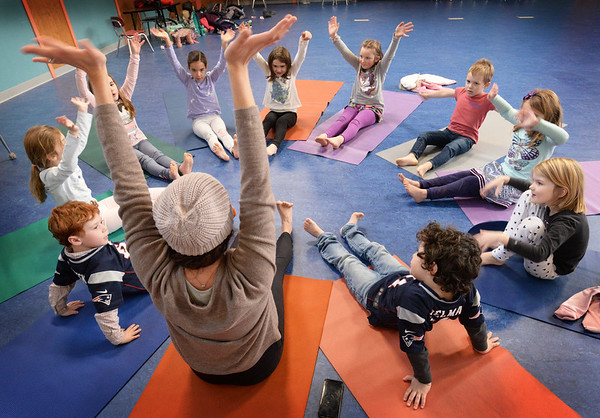 "BRYAN EATON/Staff photo. Explorations, an afterschool program at Newbury Elementary School, started again on Monday with Elissa Shoreman, back to camera, of Buddhaful Souls Yoga Studios in Rowley returning as one of several activities. He she does ""good morning, good night"" a yoga flow excercise to loosen the children's muscles."