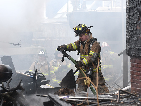JIM VAIKNORAS/Staff photo Fire fighter work in the smoke and debris at a house fire on 2nd Street in Salisbury Saturday afternoon.