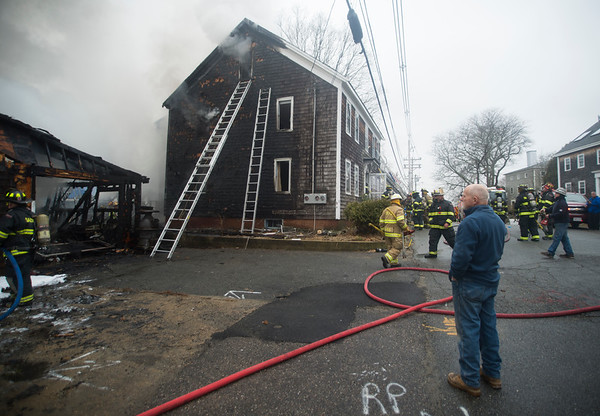 JIM VAIKNORAS/Staff photo Salisbury Harbor Master Ray Pike looks on as fire fighters battle a fire at his 2nd Street home in Salisbury Saturday.