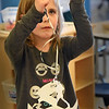 BRYAN EATON/Staff photo. While some youngsters were outside playing on real snowflakes at the Newburyport YWCA's Afterschool Program, others were inside creating their own. Lexi Ranney, 6, ties silver bow material to create a hanger for her piece of art.