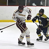 JIM VAIKNORAS/Staff photo Newburyport's Ben Reynolds bounces the puck off his stick as St Mary's Bryce Bedard closes in at the Graf Rink in Newburyport.