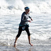 JIM VAIKNORAS/Staff photo ... takes a swim in the ocean after finishing the Hangover Classic at Salisbury Beach Tuesday. Most runners just went in knee deep due to  warnings about high surf and an undertow.