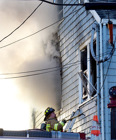 BRYAN EATON/Staff photo. A firefighter takes out the windows of the structure.