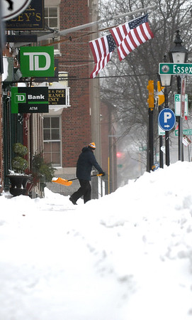 JIM VAIKNORAS/Staff photo Hayden Choate of Newburyport shovels teh sidewalk on State Street in Newburyport Sunday morning as a pair of American flags wave in the wind.