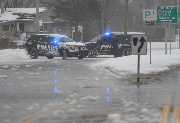 JIM VAIKNORAS/Staff photo A pair of Salisbury Police cruisers block Beach Road at high tide Sunday morning due to minor coastal flooding.
