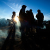 JIM VAIKNORAS/Staff photo Wood smoke clings to teh cold ground as people gather for warmth around small fires at the Old Newbury Christmas Tree Bonfire at the Tendercrop Farm fields and Spencer Perce-Little Farm in Newbury Saturday night.
