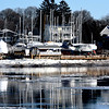 JIM VAIKNORAS/Staff photo Mast of sail boat in dry dock at Rings Island Marina in Salisbury are reflected in the Merrimac River as as ice flows by Saturday morning.