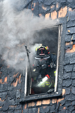 JIM VAIKNORAS/Staff photo A Hampton firefighter looks out a smoke filled window at a house fire on 2nd Street in Salisbury Saturday afternoon.