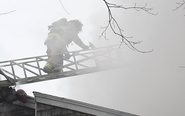 JIM VAIKNORAS/Staff photo A Salisbury fire fighter makes his way back down the ladder after venting the roof at a house fire on 2nd Street in Salisbury Saturday afternoon.