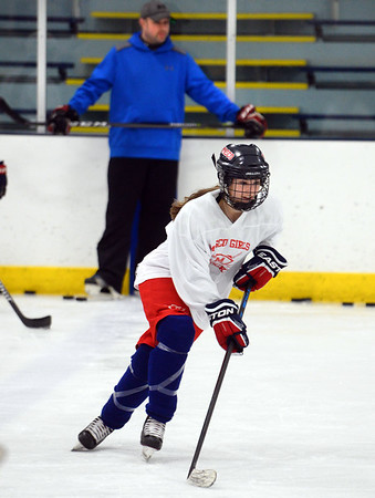 CARL RUSSO/Staff photo. Newburyport freshman Isabel Hulse is having a terrific start to her high school career, as she is currently among the leading scorers for the Masconomet girls hockey co-op team. The team's coach, Ryan Sugar is in the background. 1/24/2019.